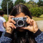 Hier seht ihr ein Mädchen mit einer Kamera. Sie drückt auf den Auslöser.