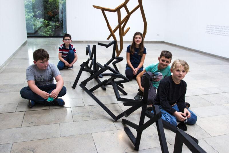 Kinder sitzen auf dem Boden neben ihrem Kunstwerk.