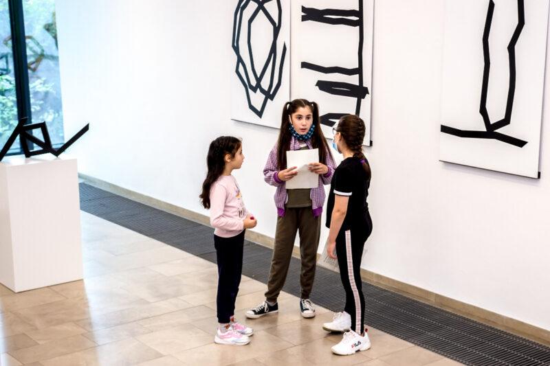 Hier seht ihr drei Mädchen vor den Zeichnungen von Robert Schad. Sie bereiten sich auf die Eröffnungsrede vor.