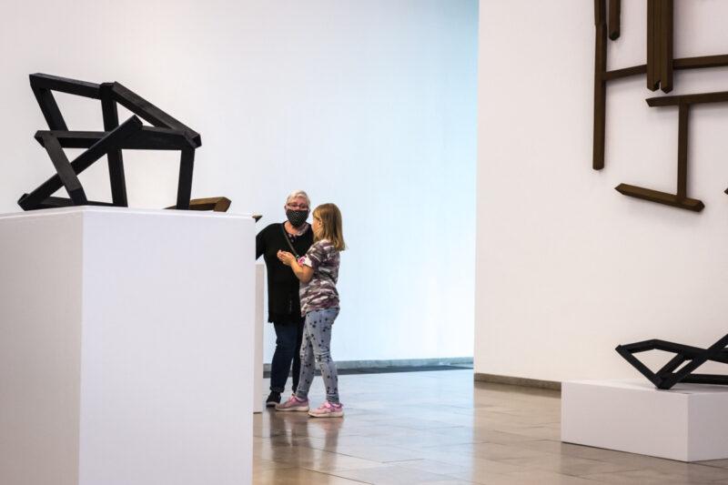 Hier sind eine Frau und ein Mädchen im Gespräch im Museum. Überall sind skulpturen zu sehen.