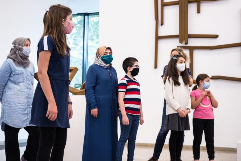 Hier seht ihr Eltern und Kinder bei der Ausstellungseröffnung. Die Ausstellung heißt I like to move it.