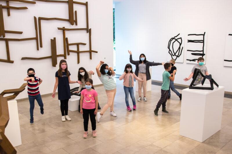 Die Kinder aus der Kunstwerkstatt stehen vor den Skulpturen im Museum und machen Tanzbewegungen