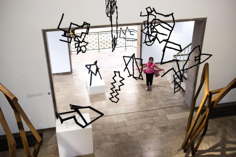 Hier seht ihr ein Mädchen im Museum. Es guckt zu uns rauf. Wir sehen Mobiles von der Decke hängen und Stahlskulpturen.