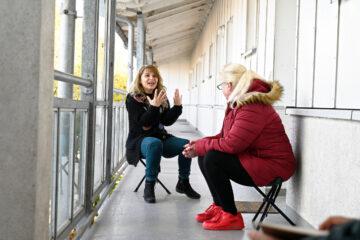 Hier seht ihr zwei Frauen, die im Hausflur sitzen. Eine Frau erzählt etwas, die andere hört zu.