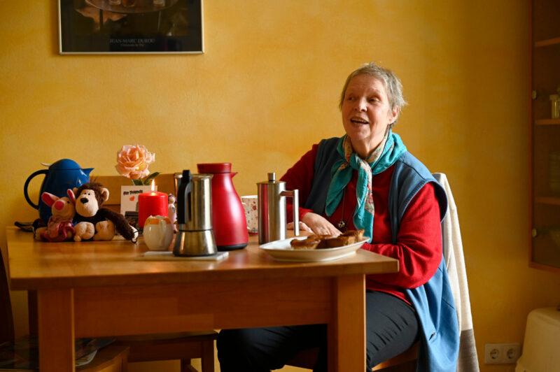 Hier seht ihr eine ältere Frau an einem gedeckten Tisch. sie erzählt gerade etwas.