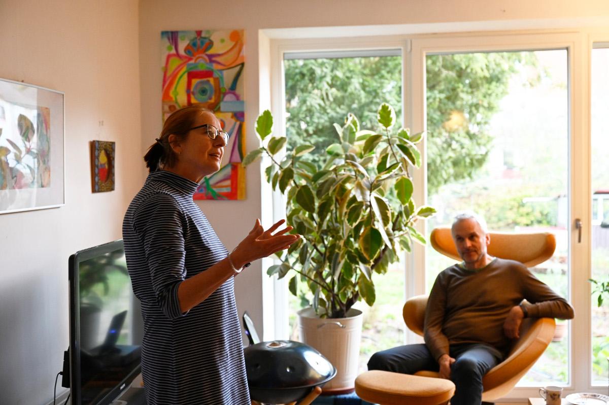 Hier seht ihr eine Frau, die etwas erzählt. Ihr Mann sitzt im Sessel und hört zu.