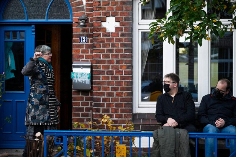 Hier sehr ihr eine Erzählerin. Sie erzählt eine Geschichte in ihrem Vorgarten. Zwei Männer hören auf der Bank sitzend zu.